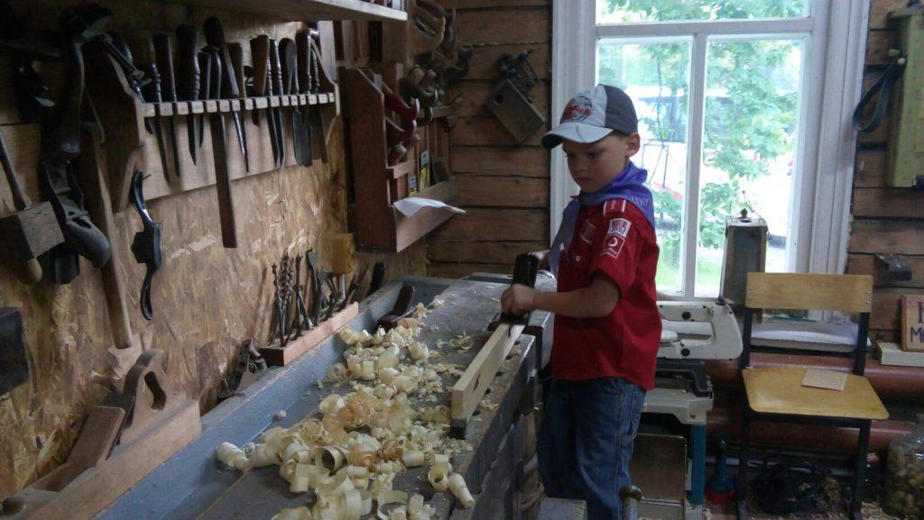 Фёдор производит стружку ручным рубанком.
